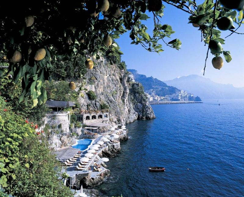 Hotel Santa Caterina Amalfi. Built into the rock and hanging over the sea, the pool is surrounded by lounge chairs and sun umbrellas. Guests can access the pool and the private beach below, using the property's private glass elevators.